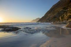 Movimiento de marea en la playa de Noordhoek en la península del cabo en Suráfrica, contra el contexto de las montañas de la pení Imagenes de archivo