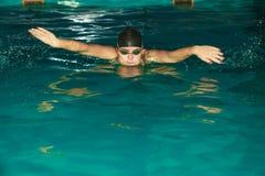 Movimiento de mariposa de la natación del atleta de la mujer en piscina Foto de archivo