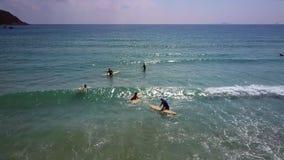 Movimiento de ondas de la playa con las personas que practica surf para abrir el océano almacen de metraje de vídeo