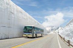 Movimiento del autobús de turistas a lo largo de la pared de la nieve de las montañas de Japón en la ruta alpina del kurobe de ta Foto de archivo