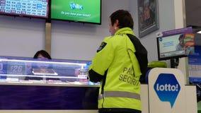 Movimiento del boleto de lotería de la compra del guardia de seguridad almacen de video