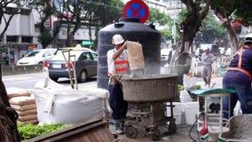 Movimiento del cemento de mezcla del trabajador para la preparación en emplazamiento de la obra almacen de video