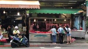 Movimiento del cliente que compra carne cruda en el mercado tradicional