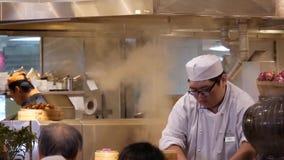Movimiento del cocinero que prepara la comida para el cliente con vapor pesado