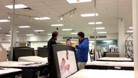 Movimiento del colchón de las compras del cliente y discusión con el vendedor metrajes