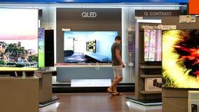 Movimiento del comprador que mira la nueva TV para comprar almacen de video