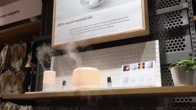 Movimiento del difusor del aceite del aroma en el estante de la venta de la exhibición