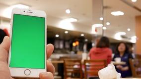 Movimiento del hombre que celebra el teléfono de pantalla verde con la gente de la falta de definición que come la comida y la ch almacen de metraje de vídeo