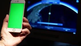 Movimiento del hombre que celebra el teléfono elegante de la pantalla verde