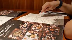Movimiento del menú de la lectura de la mujer para la comida que ordena dentro del restaurante chino almacen de video