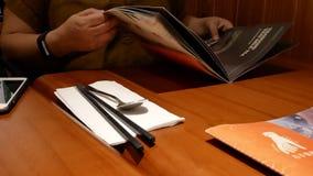 Movimiento del menú de la lectura de la mujer para la comida que ordena dentro del restaurante chino metrajes