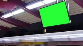 Movimiento del MRT que pasa por la plataforma en la noche con el tablero verde del tráfico de la pantalla metrajes