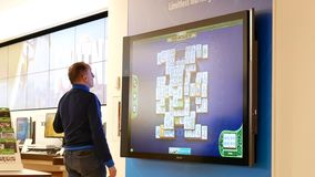 Movimiento del padre y de los niños que juegan al juego del xbox en la pantalla de la TV en la tienda de Microsoft almacen de video