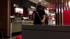 Movimiento del piso de la limpieza del trabajador delante de la máquina de la soda del servicio del uno mismo