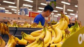 Movimiento del plátano de la media del vendedor en el estante de exhibición metrajes