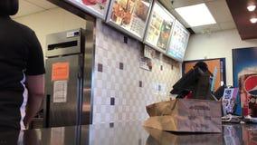 Movimiento del pollo que ordena de la gente dentro del restaurante de KFC almacen de metraje de vídeo