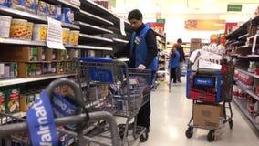 Movimiento del precio cambiante del vendedor del ultramarinos dentro de la tienda de Walmart almacen de metraje de vídeo