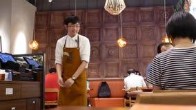 Movimiento del recibo que da del camarero hacia fuera para el cliente