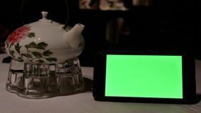 Movimiento del teléfono de pantalla verde con la gente de la falta de definición que come la comida dentro del restaurante almacen de video