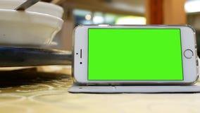 Movimiento del teléfono de pantalla verde con la tabla de torneado de la gente para comer la comida