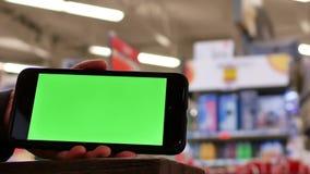 Movimiento del teléfono de pantalla verde delante del sofá de la exhibición almacen de metraje de vídeo