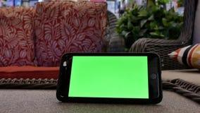 Movimiento del teléfono de pantalla verde delante del sofá de la exhibición almacen de video