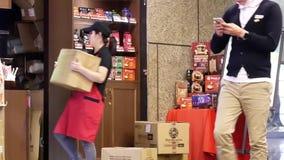 Movimiento del trabajador que almacena la materia y que sirve el café para el cliente almacen de video
