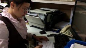 Movimiento del trabajador que da el recibo para el paciente en el área de recepción médica metrajes