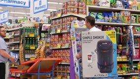 Movimiento del trabajador que exhibe la bebida en el estante de exhibición para la venta almacen de video