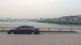 Movimiento en el puente sobre el río, alto tráfico Vida de ciudad grande Vista de una metrópoli típica en Asia metrajes