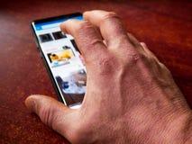 Movimiento en sentido vertical caucásico envejecido de la mano del hombre, buscando en smartphone moderno fotografía de archivo