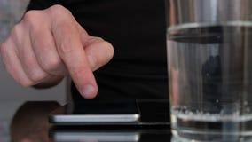 Movimiento en sentido vertical de la mano del hombre en un smartphone al lado de un vaso de agua C?mara lenta almacen de video
