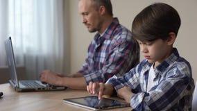 Movimiento en sentido vertical del muchacho en la tableta, padre que trabaja en el ordenador portátil, falta de atención metrajes