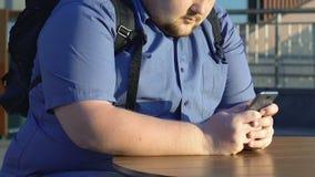 Movimiento en sentido vertical gordo del estudiante masculino en smartphone, solamente en el café de la calle, primer almacen de video