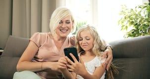 Movimiento en sentido vertical Smartphone de la madre y de la hija almacen de video