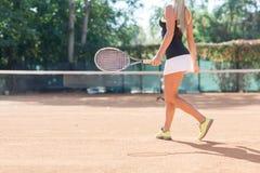 Movimiento femenino rubio del jugador de tenis por un campo de tenis al aire libre Imagenes de archivo