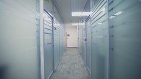 Movimiento a lo largo del vestíbulo entre las oficinas con las paredes de cristal almacen de video
