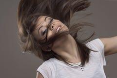 Movimiento parado de la morenita joven hermosa del pelo recto que lanza el pelo y que mira el camer fotos de archivo