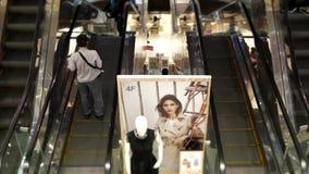 Movimiento rápido de la gente que toma la escalera móvil dentro del centro comercial en Taiwán