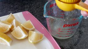 Movimiento rápido de la mujer que exprime el jugo de limón en la taza de medición