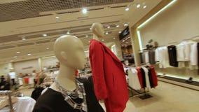 Movimiento rápido a través de la tienda y foco en maniquí en chaqueta roja