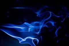 Movimiento t?xico azul de los humos en un fondo negro imágenes de archivo libres de regalías