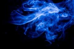 Movimiento t?xico azul de los humos en un fondo negro fotografía de archivo