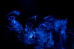 Movimiento t?xico azul de los humos en un fondo negro fotos de archivo