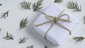 Movimientos de la cámara adelante en la caja de regalo blanca de la artesanía y ramas frescas del abeto en el fondo blanco metrajes