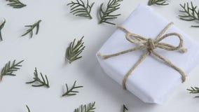 Movimientos de la cámara adelante en la caja de regalo blanca de la artesanía y ramas frescas del abeto en el fondo blanco almacen de metraje de vídeo