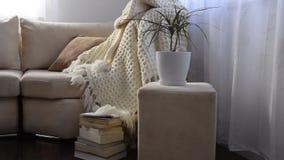 Movimientos de la cámara a lo largo de invitar el sofá cómodo con la manta y los libros de lana hechos a mano almacen de video