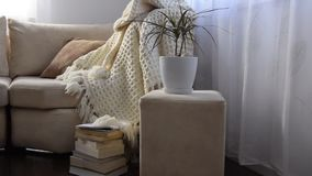 Movimientos de la cámara a lo largo de invitar el sofá cómodo con la manta y los libros de lana hechos a mano almacen de metraje de vídeo