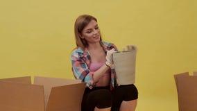 Movimientos de la muchacha y cosas y maceta del paquete metrajes