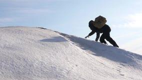Movimientos del hombre al top a su éxito El escalador sube la montaña nevosa en rayos del sol brillante el turista hace subida pa almacen de metraje de vídeo
